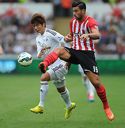 Southampton's Graziano Pelle passes the ball away from Swansea City's Ki Sung-Yueng - Photo mandatory by-line: Alex James/JMP - Mobile: 07966 386802 20/09/2014 - SPORT - FOOTBALL - Swansea - Liberty Stadium - Swansea City v Southampton  - Barclays Premier League