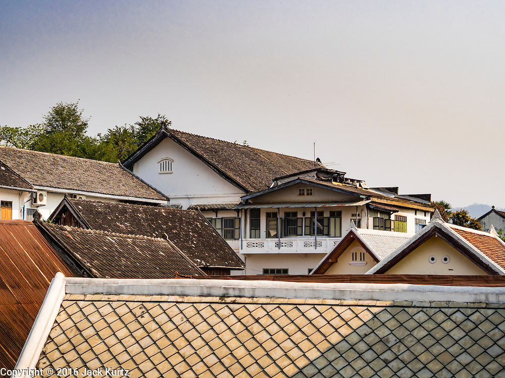 "13 MARCH 2016 - LUANG PRABANG, LAOS: The roofline of colonial era buildings that have been renovated into tourist hotels, spas and restaurants in Luang Prabang. Luang Prabang was named a UNESCO World Heritage Site in 1995. The move saved the city's colonial architecture but the explosion of mass tourism has taken a toll on the city's soul. According to one recent study, a small plot of land that sold for $8,000 three years ago now goes for $120,000. Many longtime residents are selling their homes and moving to small developments around the city. The old homes are then converted to guesthouses, restaurants and spas. The city is famous for the morning ""tak bat,"" or monks' morning alms rounds. Every morning hundreds of Buddhist monks come out before dawn and walk in a silent procession through the city accepting alms from residents. Now, most of the people presenting alms to the monks are tourists, since so many Lao people have moved outside of the city center. About 50,000 people are thought to live in the Luang Prabang area, the city received more than 530,000 tourists in 2014.    PHOTO BY JACK KURTZ"