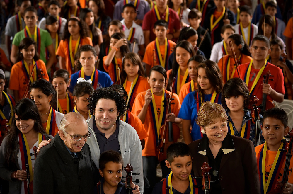 (Left to Right)  Antonio Abreu, Gustavo Dudamel, and Deborah Borda, President and Chief Executive Officer of the Los Angeles Philharmonic, pose for a portrait with an orchestra of children trained by El Sistema, Venezuela's internationally acclaimed, state-funded classical music education program that serves underpriviledged children.
