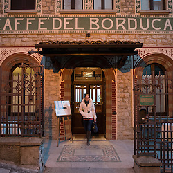 A woman comes out of Caffè del Borducan in Santa Maria del Monte near Varese, Italy