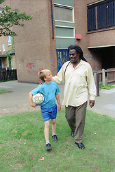 Boy and carer walking together outside block of flats; talking,