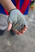 Boy age 8 holding Polish coins in his fingerless bicycle gloves. Rzeczyca Central Poland