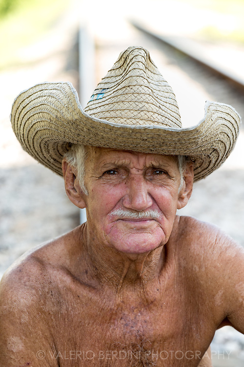 A cart owner poses for a portrait on a railway track in Santa Clara, Cuba.