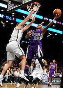 Sacramento Kings' Isaiah Thomas (22) aims for the basket over Brooklyn Nets' Mirza Teletovic (33) during an NBA basketball game on Sunday, March 9, 2014 at Barclays Center in New York. (AP Photo/Kathy Kmonicek)