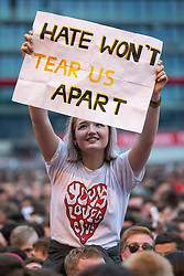 """© Licensed to London News Pictures . 27/05/2017 . Manchester , UK . A woman holds up a hand painted sign reading """" HATE WON'T TEAR US APART """" during the Courteeners' set . Manchester music line up , featuring Courteeners , Charlatans , Blossoms and Cabbage , at the Emirates Old Trafford Stadium . Photo credit : Joel Goodman/LNP"""