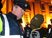 A masked man 'with three kids under four' argues with a policeman about his thoughts on the Irish budget during protests on Merrion Street in Dublin, Ireland.