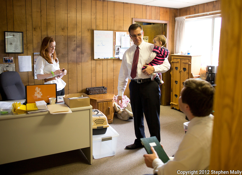 Rep. Bobby Schilling (R-Ill) talks with his son and campaign manager, Terry Schilling (right) while holding Terry's daughter, Reagan, 10 months, as Katie Schilling (left), campaign finance director, glances at her phone at his campaign headquarters in East Moline, Illinois on Monday, April 30, 2012. Katie Schilling is the wife of Terry Schilling.