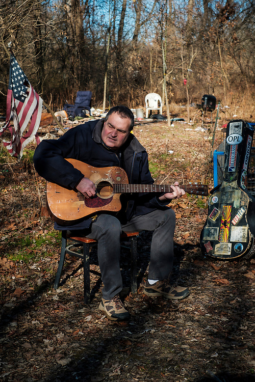 ELKTON, MARYLAND - DECEMBER 26: Zane Cambell plays his guitar in a deserted homeless encampment in the woods near his home in Elkton, Maryland on Tuesday, December 26, 2017 in Elkton, Maryland. Campbell likes to talk about how he feels his life is in shambles after a long history of alcoholism. Campbell was born into one of the most revered clans of old-time country music. His aunt was the legendary singer-songwriter Ola Belle Reed, and his uncle was Alex Campbell, a bluegrass singer who hosted shows at the country music parks along the Pennsylvania/Maryland border. (Photo by Pete Marovich For The Washington Post)