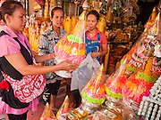 "05 JULY 2011 - BANGKOK, THAILAND:      Women shop for supplies for Buddhist rites in a shop on Bamrung Muang Street in Bangkok. Thanon Bamrung Muang (Thanon is Thai for Road or Street) is Bangkok's ""Street of Many Buddhas."" Like many ancient cities, Bangkok was once a city of artisan's neighborhoods and Bamrung Muang Road, near Bangkok's present day city hall, was once the street where all the country's Buddha statues were made. Now they made in factories on the edge of Bangkok, but Bamrung Muang Road is still where the statues are sold. Once an elephant trail, it was one of the first streets paved in Bangkok, it is the largest center of Buddhist supplies in Thailand. Not just statues but also monk's robes, candles, alms bowls, and pre-configured alms baskets are for sale along both sides of the street.       PHOTO BY JACK KURTZ"