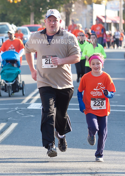 Cornwall-on-Hudson, New York - A girl in the Girls on the Run Hudson Valley program and her running buddy run in the Cornwall Lions Club Fall Harvest Race 5K on Nov. 10, 2013. Girls on the Run is a national program with a mission of helping girls to be joyful, healthy and confident using an experience-based curriculum which creatively integrates running.