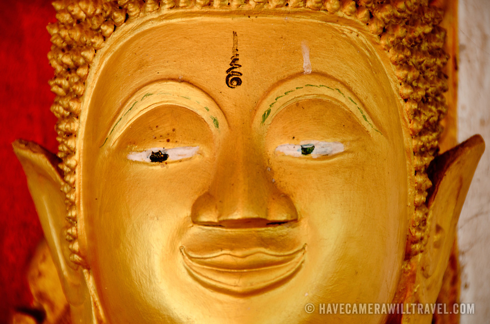 Face of a golden statue of The Buddha at a Wat (Buddhist Temple) in Vientiane, Laos. This statue is in the Cambodian style. Frontal view of face.