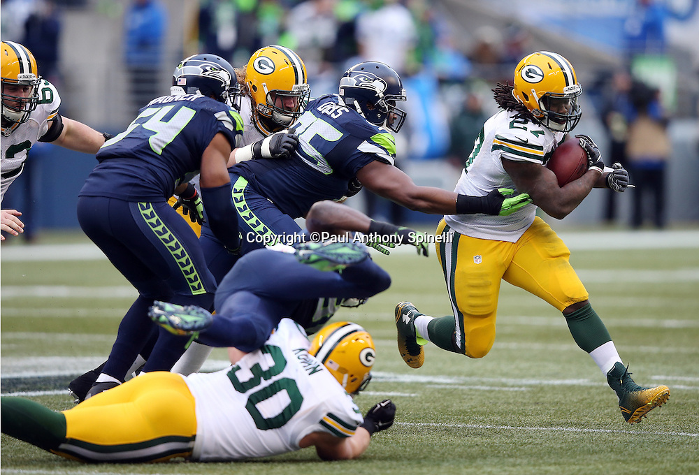 Green Bay Packers running back Eddie Lacy (27) runs for a fourth quarter gain of 5 yards as he eludes the outstretched arm of Seattle Seahawks tight end Demarcus Dobbs (95) during the NFL week 20 NFC Championship football game against the Seattle Seahawks on Sunday, Jan. 18, 2015 in Seattle. The Seahawks won the game 28-22 in overtime. ©Paul Anthony Spinelli