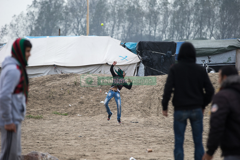October 24, 2016 - Calais, Calais, France - Calais , France . People play with a tennis ball in the Jungle migrant camp in Calais , Northern France , underway , on the day of a planned eviction and start of the destruction of the camp  (Credit Image: © Joel Goodman/London News Pictures via ZUMA Wire)
