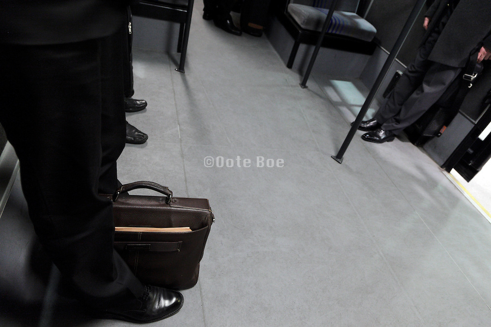 businessmen with briefcase standing waiting in a bus