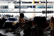 Frankfurt am Main | April 19 2010<br /> Durch eine riesige Aschewolke, die durch einen Ausbruch von Vulkan Eyjafjallajoekull auf Island ausgestossen wurde, kommt der Flugverkehr ueber fast ganz Europa zum Erliegen, etwa 800 Fluggaeste sind im Transit in Terminal 1 gestrandet, sie haben kein Visum und koennen nicht nach Deutschland einreisen. Hier: Ein gestrandeter Passagier ruht sich auf seinem Feldbett aus, im Hintergrund ein Flugzeug auf dem Vorfeld. @peter-juelich.com [No Model Release | No Property Release]