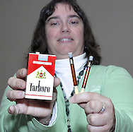 "Tobacco Cessation Specialist Alison Diver, holds a demonstration pack of cigarettes and tubes showing ""the amount of tar that collects in your lungs after you smoke a pack of cigarettes"" after a smoking cessation counseling session at Samaritan North Health Center, Thursday, November 1, 2007."