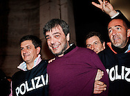 """ITALY, Naples : Italian policemen celebrate as they escort Antonio Iovine, one of the most powerful leaders of the Camorra organised crime group, after his arrest after 14 years on the run, on November 17, 2010 in Naples. Iovine, believed to be the boss of the murderous Casalesi clan, was nabbed in Casal di Principe, the clan's home town north of Naples. He had been on the interior ministry's most wanted list for years. Iovine was found in a home in Casal di Principe after """"complex"""" police work and he did not resist arrest, a ANSA news agency's report said. AFP PHOTO / ROBERTO SALOMONE"""