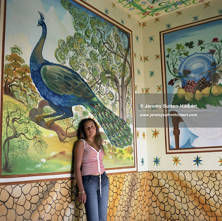 """Nadia, a 14 years old Roma girl, stands  posing like a """"western"""" model in front of a mural depicting a peacock painted on the wall of her parents home, in the new part of Sintesti Roma camp. Two weeks after this picture was taken Nadia was due to be married..."""