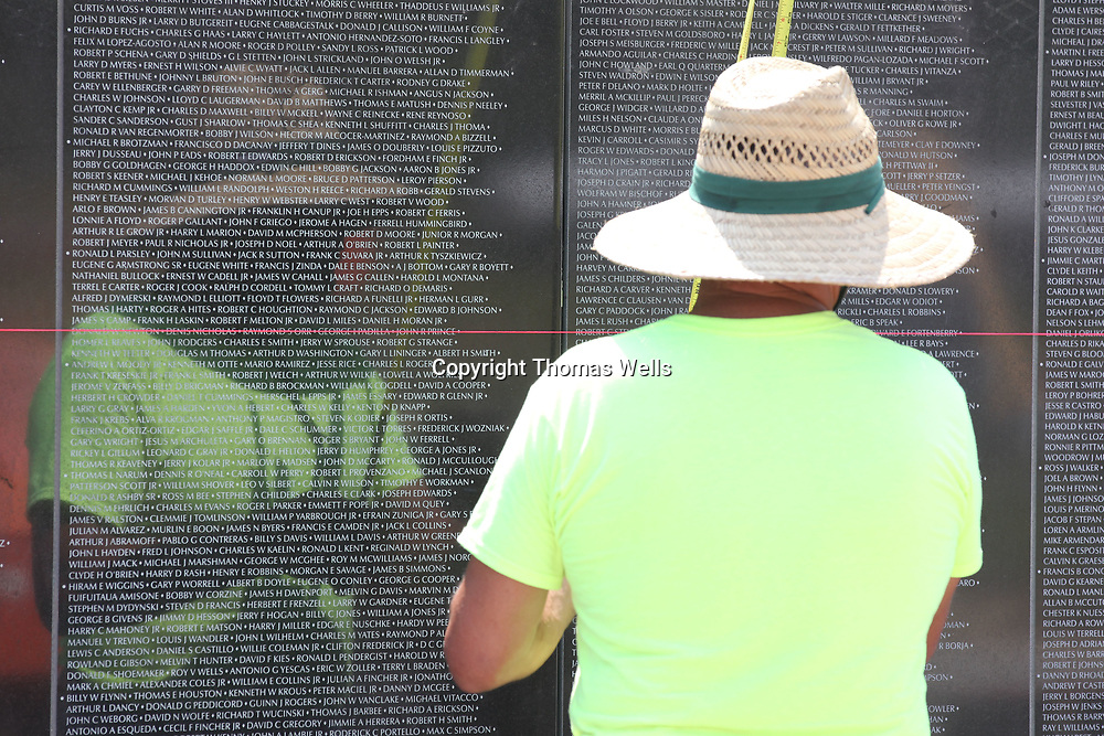 Rob Coulon of Harvey Louisiana is reflected behind the names of those listed on the new Vietnam Memorial Wall being constructed at Veterans Park in Tupelo.