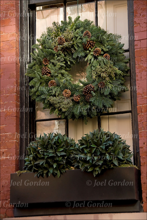 Christmas Wreath and decorations on front window in Greenwich Village.<br /> <br /> The tradition of hanging wreath during Christmas is essentially a Christian ritual. This is done during the Christmas season, traditionally used to prepare for the coming of Christ, also known as the Advent season in Christianity. Traditionally, the Christmas wreaths were made of evergreen leaves, which are still symbolize the permanence of life. A traditional wreath is a circle, which means that there is no beginning or end and that God is eternal.