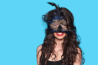 Portrait of a young woman wearing exotic eye mask over blue background