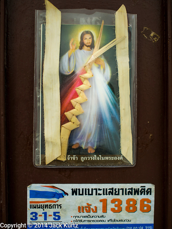 """28 OCTOBER 2014 - BANGKOK, THAILAND: The doorway to a Catholic home in Thonburi section of Bangkok near the Pajonglak Maneeprasit Bakery. The bakery makes cakes called """"Kanom Farang Kudeejeen"""" or """"Chinese Monk Candy."""" The tradition of baking the cakes, about the size of a cupcake or muffin, started in Siam (now Thailand) in the 17th century AD when Portuguese Catholic priests accompanied Portuguese soldiers who assisted the Siamese in their wars with Burma. Several hundred Siamese (Thai) Buddhists converted to Catholicism and started baking the cakes. When the Siamese Empire in Ayutthaya was sacked by the Burmese the Portuguese and Thai Catholics fled to Thonburi, in what is now Bangkok. The Portuguese established a Catholic church near the new Siamese capital. Now just three families bake the cakes, using a recipe that is 400 years old. The same family has been baking the cakes at the Pajonglak Maneeprasit Bakery, near Santa Cruz Church, for more than 245 years. There are still a large number of Thai Catholics living in the neighborhood around the church.   PHOTO BY JACK KURTZ"""