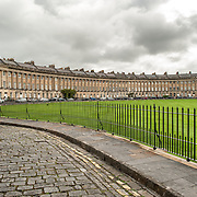 A cobblestone road runs in front of the Royal Crescent in Bath, Somerset. The Royal Crescent is a street of 30 terraced houses laid out in a sweeping crescent in the city of Bath, England. Designed by the architect John Wood the Younger and built between 1767 and 1774, it is among the greatest examples of Georgian architecture to be found in the United Kingdom and is a Grade I listed building. Although some changes have been made to the various interiors over the years, the Georgian stone façade remains much as it was when it was first built.