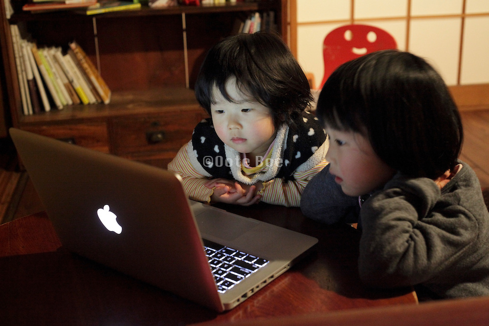 two Japanese toddlers watching concentrated program on laptop computer