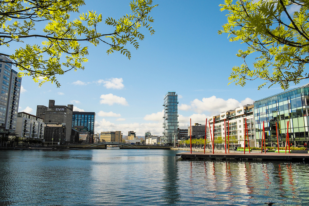 Dublin City, Ireland: An image of the new buildings and old mill of Grand Canal Dock, and Grand Canal Quay in Dublin's Docklands district framed by trees in the foreground