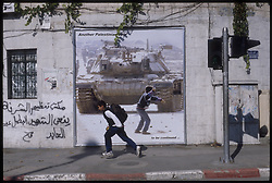 A Palaestinian boy, on his way home from school, runs by a life sized poster glorifying the Intifada, while just a few meters away, Palestinian youths engage in clashes with Israeli soldiers, in the West-bank city of Ramallah. (Photo © Jock Fistick)