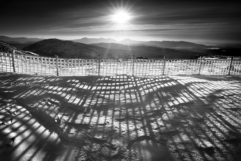 Long shadows cast by a fence coated wind driven rime frost formations on Arening Fawr, Snowdonia.