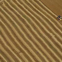 Aerial view of a farmer near Auchterarder, Perthshire at work on his fields in a combine harvester.<br />