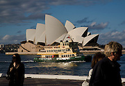 The Opera House from the water front of the overseas passager terminal in circular quay. Sydney harbour ferry makes it's way into circular quay.