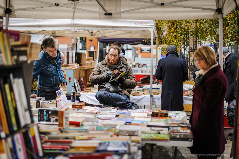 A bookseller sits at his stand in the middle of a busy market stall selling books. Located at at the regular market that takes place in Dublin's Temple Bar district