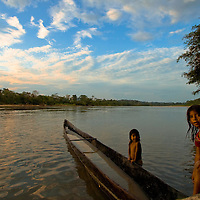 Girls play around a canoe at sunset in the Napo river of Amazonian Ecuador