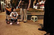 """Dans une rue de l'ile de Shamian, Emmalee (7 ans) avec ses parents adoptifs Marvin et April. Emmalee est atteinte de Phocomelia une maladie congnitale qui resulte en une atrophie des jambes. Emmalee est le 6 eme enfant adopte par Marvin et April. Tous sont handicapes. Marvin et Apri, ont egalement trois enfants biologiques. L'adoption de Emmalee leur a coute 24 000 $. Ils n'ont pas visite  l'orphelinat ou etait Emmalee. Il leur aurait fallu debourser 300$ pour cela. """"Tout est une question d'argent"""" dit April."""