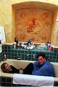 "Actress and writer Carrie Fisher poses for a photo with the ""Painter to the Stars "", Michael Bell, in the bathtub in Fisher's home with the mural Bell painted."