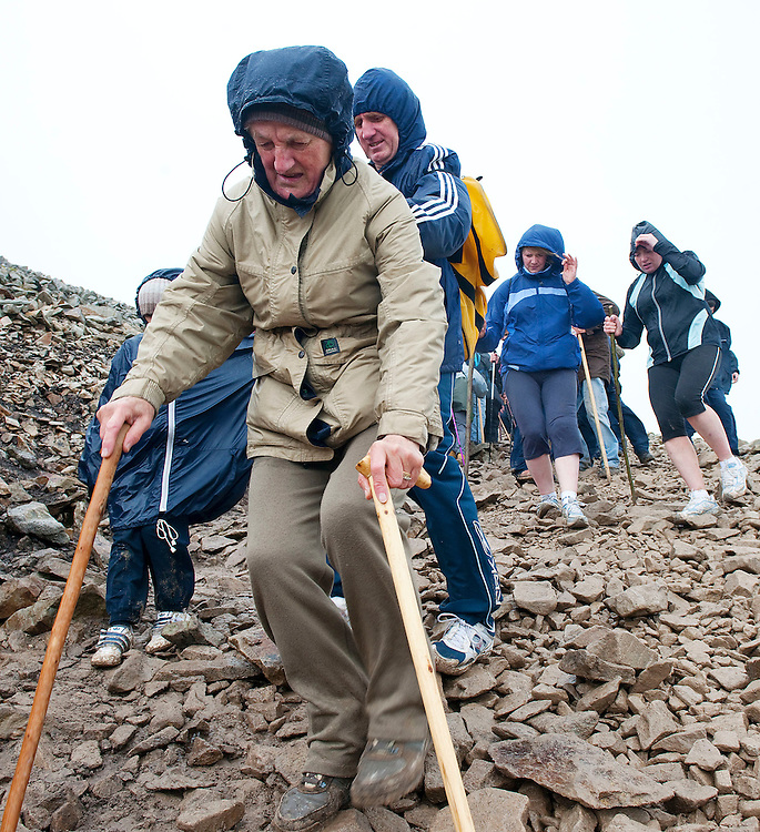 Kitty Creaby from Achill Island makes her way down the mountain with the help of her son Eddie and Great Grandson Rhys,   annual pilgrimage to  Croagh Patrick, Co. Mayo. Pic: Michael Mc Laughlin Thousands of pilgrims navigate up and down the rugged slopes of croagh Patrick in honour of our Patron Saint, Saint Patrick, Ireland's Holy Mountain, Co. Mayo. Pic: Michael Mc Laughlin