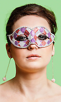 Portrait of beautiful young woman wearing eye mask against green background
