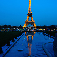 The Eiffel Tower is seen lit up at dusk in Paris, France, in April, 2015.