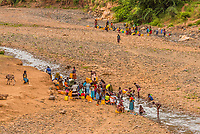 Women bathing in a shallow river and collect water into containers, Southern Nations Nationalities and People's Region, Ethiopia.