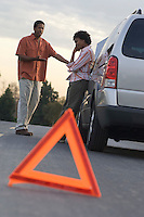 Warning triangle in front of broken down car, people in background