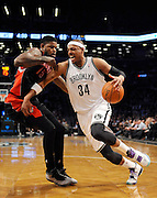 Brooklyn Nets' Paul Pierce (34) drives the ball around Toronto Raptors' Amir Johnson (15) during an NBA basketball game on Monday, March 10, 2014 at Barclays Center in New York. (AP Photo/Kathy Kmonicek)