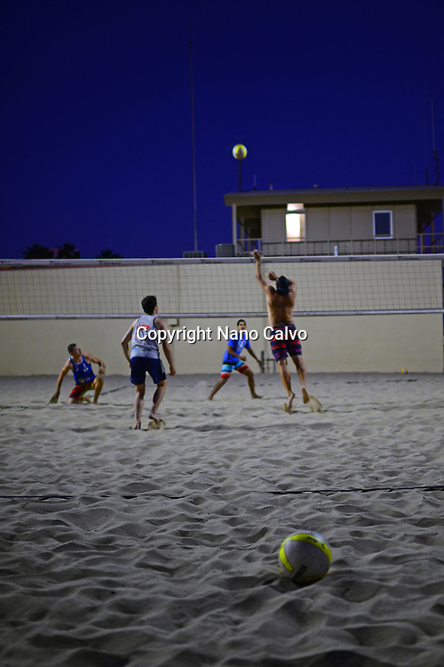 Group of young people playing beach volleyball in Santa Monica beach, California.