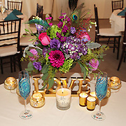A sweetheart table decorated with gold candles, custom painted peacock feather champagne glasses, and a brightly colored floral centerpiece -- The sweetheart table was at a wedding held at Anyela's Vineyard in Skaneateles, NY in the Finger Lakes