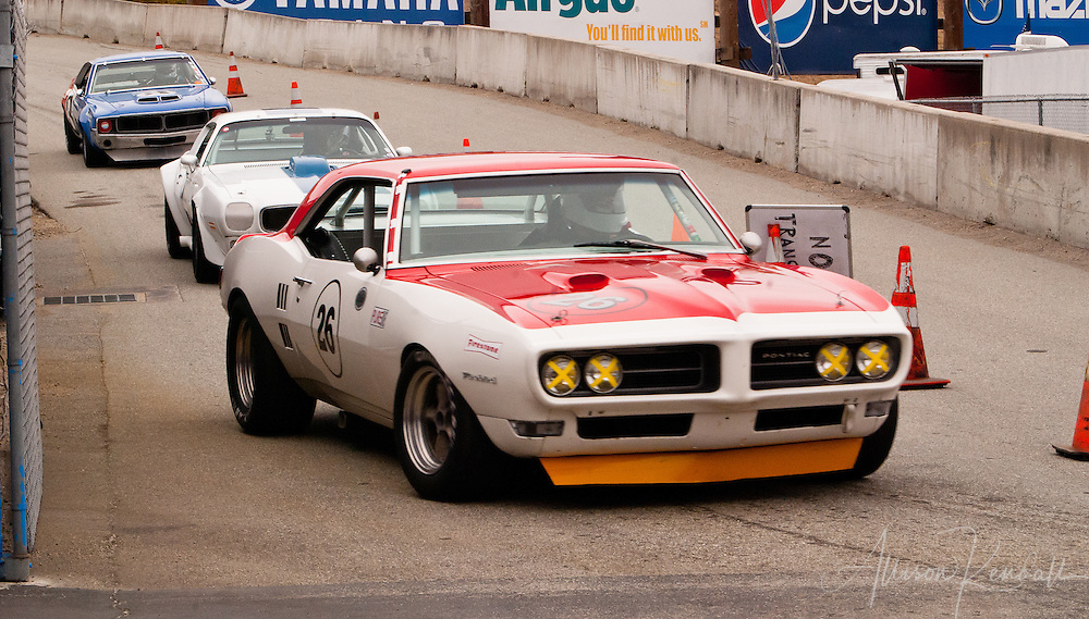 Vintage muscle cars exit the track after a race at Laguna Seca during the Reunion events of Monterey Car Week