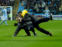 Photo: Leigh Quinnell.<br /> Coventry City v Ipswich Town. Coca Cola Championship.<br /> 19/11/2005. A coventry fan is brought to ground after getting on to the pitch.