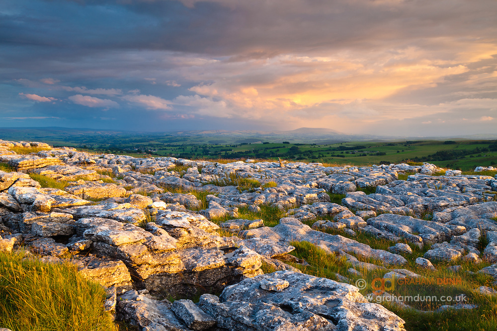 Dramatic evening skies over Pendle Hill as seen from Malham Lings' limestone pavament. Yorkshire Dales, UK