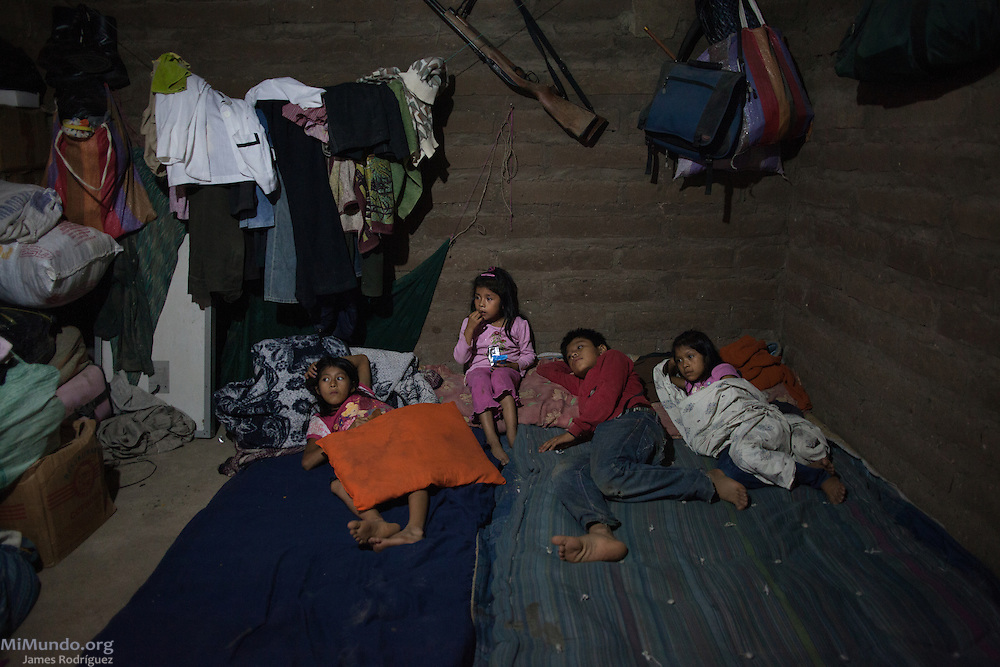 From left to right: Nuria (10), Adaly (5), Eswin (12) and Paulina (7), watch TV at home in Rio Negro. They are the four youngest children of Rio Negro massacre survivor Sebastian Iboy Osorio and Magdalena Alvarax. Nearly 400 Achi Mayan residents of Rio Negro were killed due to the community's resistance to give up their lands and make way for the Chixoy hydroelectric project. Iboy Osorio returned to Rio Negro in the early 1990s along with two other survivors and have currently grown into a community of 24 homes. Electric service was finally established in August 2015, but each house was charged 2,150 Quetzales (US $280), something they believed should be waived considering their original town was flooded to make way for a hydroelectric project. Rio Negro, Rabinal, Baja Verapaz, Guatemala. October 16, 2015.