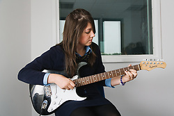 Secondary school student playing an electric guitar in a music lesson,